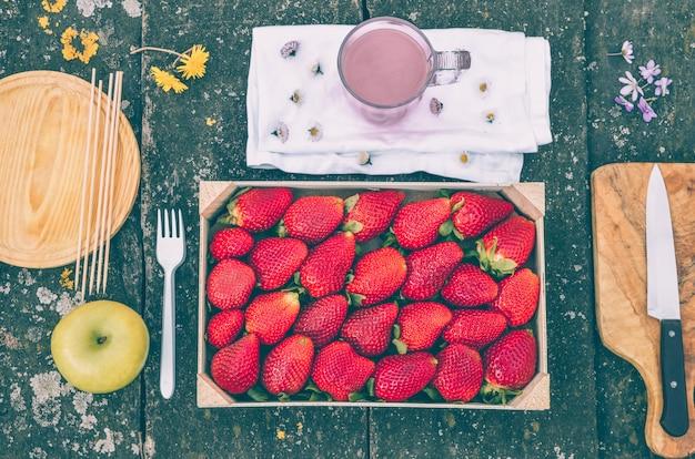 Caixa de morangos em uma mesa rústica no campo com um milkshake de morango e mais utensílios