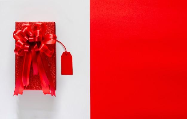 Caixa de natal vermelha com fita de laço vermelho e etiqueta de preço em branco e vermelho.
