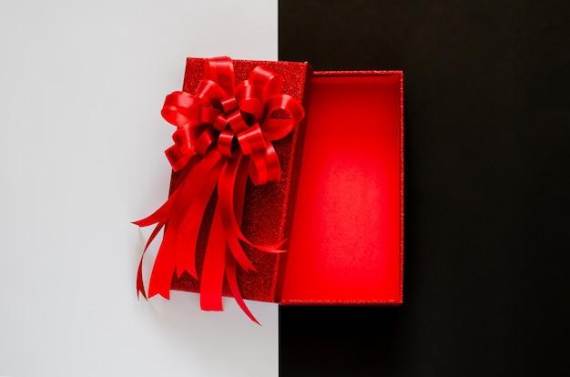 Caixa de natal vermelha com fita de laço vermelho em preto e branco.