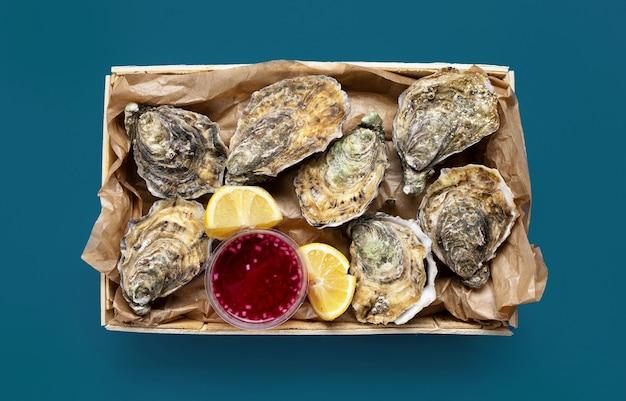 Caixa de ostras frescas abertas, molho de cebola com limão e vinagre no fundo azul, vista de cima