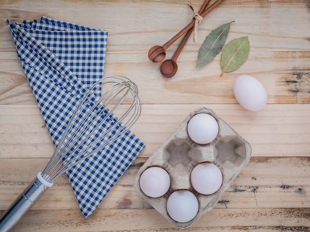 Caixa de ovo de papelão com ovos no fundo de madeira velha.