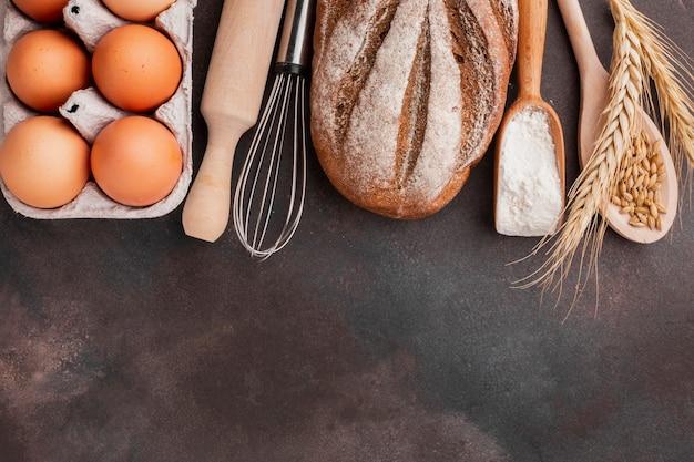Caixa de ovos com batedor e pão assado