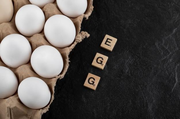 Caixa de ovos de papelão com ovos de galinha branca em uma mesa preta.