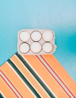 Caixa de ovos no tapete contra o pano de fundo azul