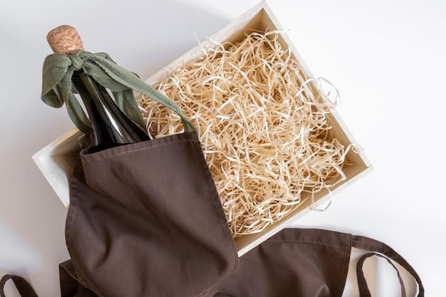Caixa de palha avental de serviço garrafa vinho fundo branco armazenamento embalagem marrom