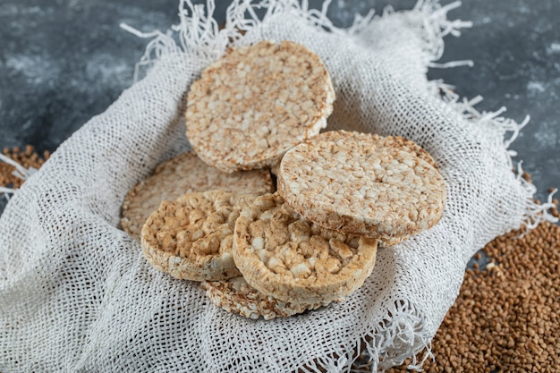 Caixa de pão crocante arejado e trigo sarraceno cru na superfície de mármore
