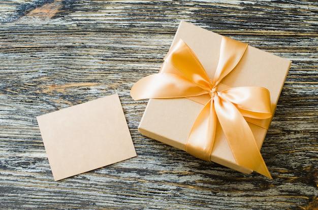 Caixa de papel artesanal de presente com fita de laço e tag em branco.