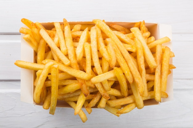 Caixa de papel com pilha de batatas fritas apetitosas sobre fundo de tábuas brancas