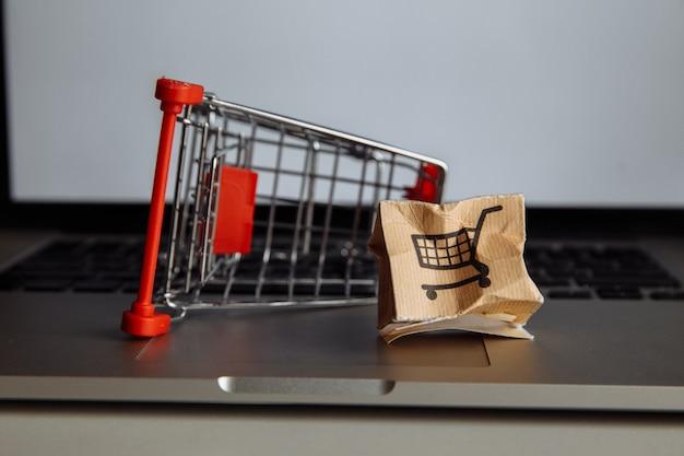 Caixa de papel e carrinho de compras danificados em um teclado de laptop. conceito de compra e entrega online.