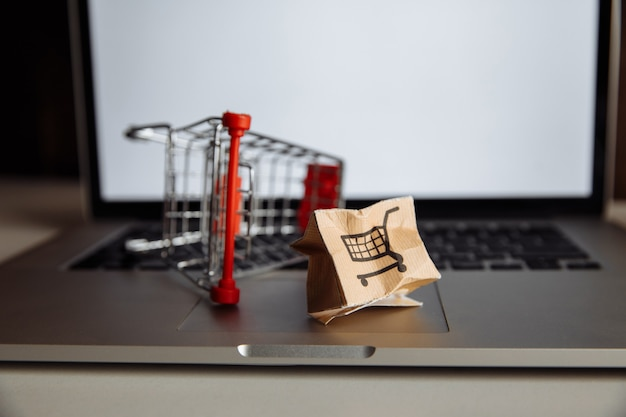 Caixa de papel e carrinho de compras danificados em um teclado de laptop. conceito de entrega. acidente de embarque.