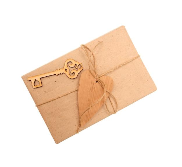 Caixa de papel kraft e coração de madeira em fundo branco.