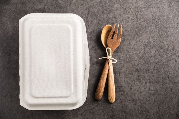 Caixa de papel para takeaway com colher e garfo de madeira no antigo fundo de mármore