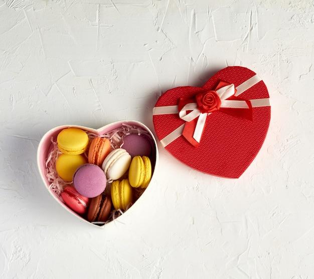Caixa de papelão aberta com uma sobremesa assada macarons redondos multicoloridos
