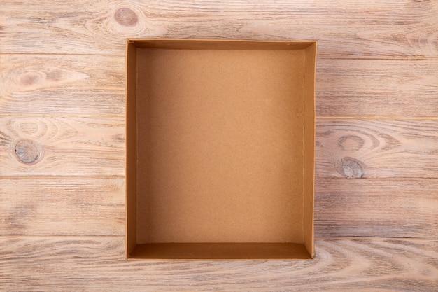 Caixa de papelão aberta na superfície de madeira