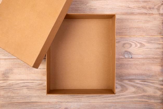 Caixa de papelão aberta sobre uma mesa de madeira. vista do topo