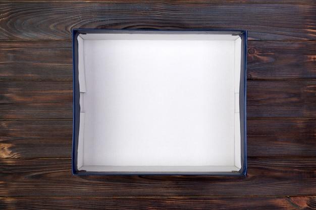 Caixa de papelão branca aberta vazia para mock up na mesa de madeira escura com espaço de cópia