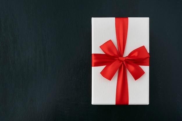 Caixa de papelão branca com fita vermelha em preto