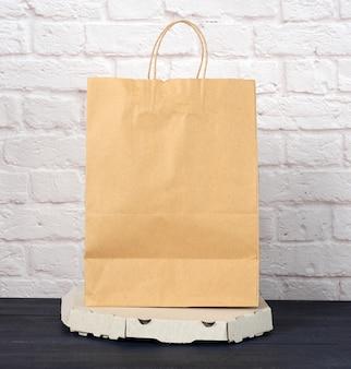 Caixa de papelão branca com pizza e saco de papel descartável