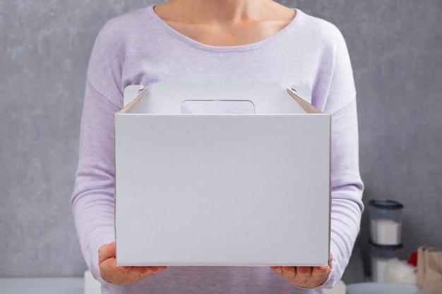 Caixa de papelão branca nas mãos. embalagens para bolos e pastéis. embalagem de alimentos. copie o espaço