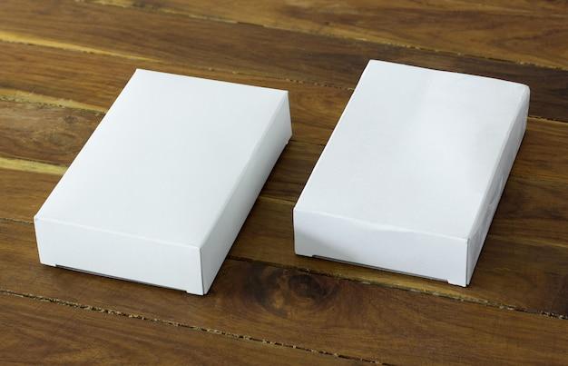 Caixa de papelão branco em branco na mesa de madeira escura