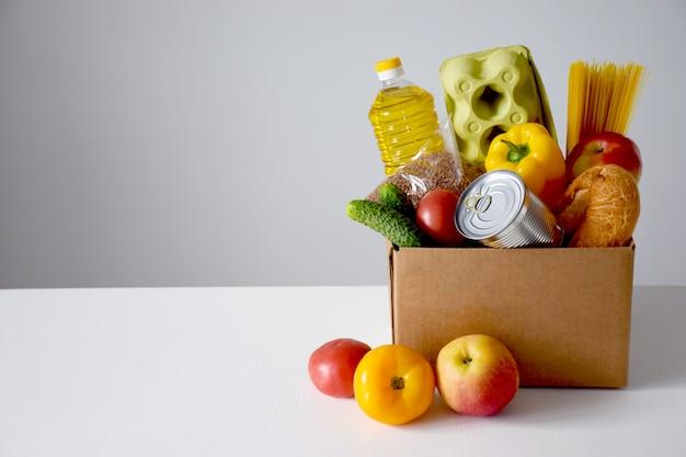 Caixa de papelão com alimentos, óleo, pão, ovos, tomate, maçã, pepino, lata, espaguete