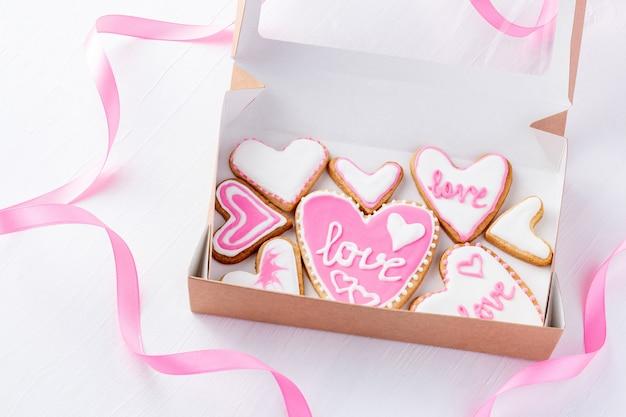 Caixa de papelão com biscoitos em forma de coração cobertos com glacê de açúcar para o dia de são valentim