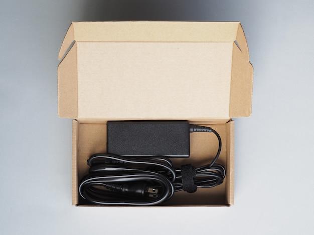 Caixa de papelão com novo carregador de bateria para laptop