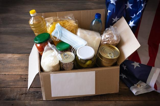 Caixa de papelão com óleo enlatado, cereais e massas