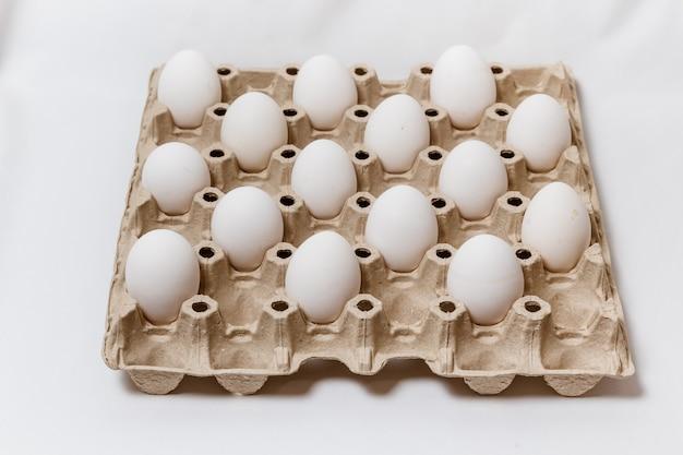 Caixa de papelão com ovos brancos distanciados no conceito de regras de quarentena de fundo branco