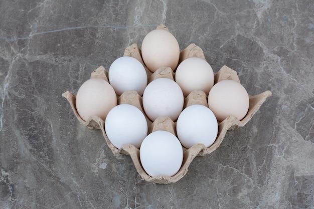 Caixa de papelão com ovos de galinha branca e penas. foto de alta qualidade