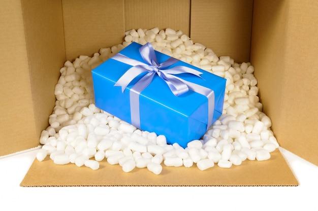 Caixa de papelão com peças de embalagem de poliestireno e presente azul.