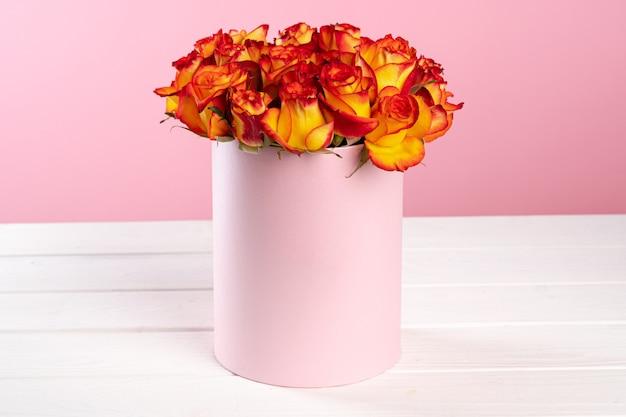 Caixa de papelão com rosas em fundo rosa