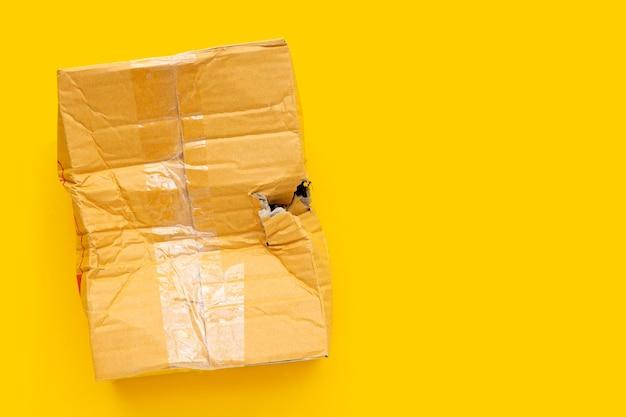 Caixa de papelão danificada com furo no fundo amarelo.