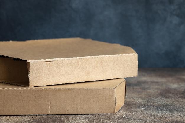 Caixa de papelão de pizza na mesa escura