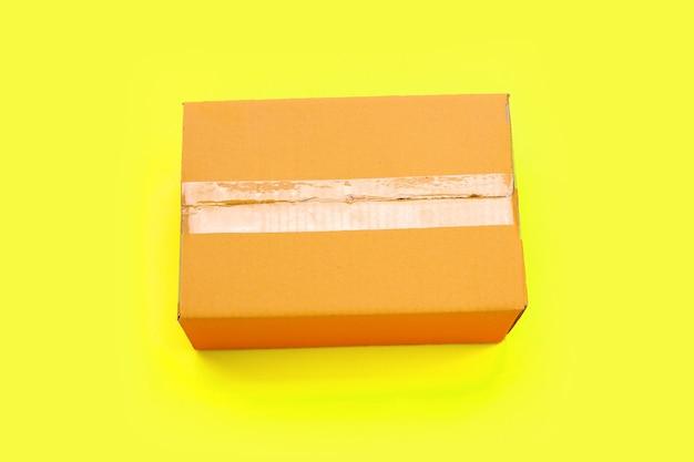 Caixa de papelão em fundo amarelo.