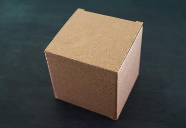 Caixa de papelão em uma mesa de madeira preta.