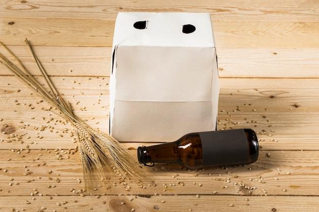 Caixa de papelão; garrafa de cerveja e espigas de trigo na superfície de madeira