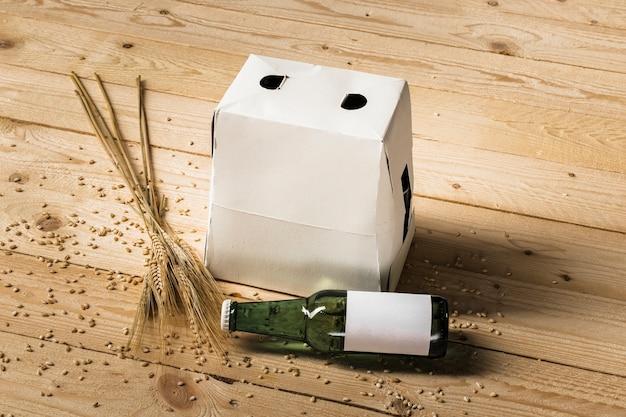 Caixa de papelão; garrafa de cerveja verde e espigas de trigo na prancha de madeira