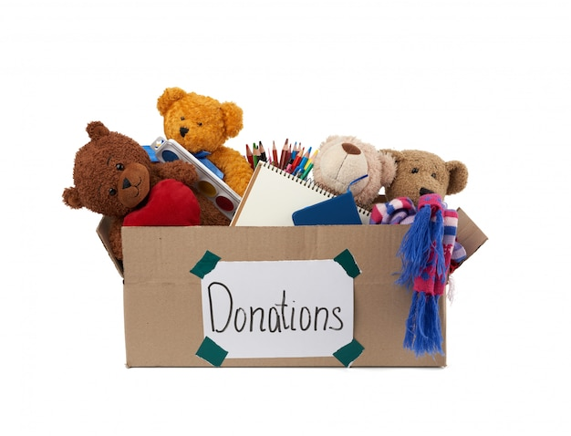 Caixa de papelão marrom cheia de brinquedos macios, material escolar na superfície branca