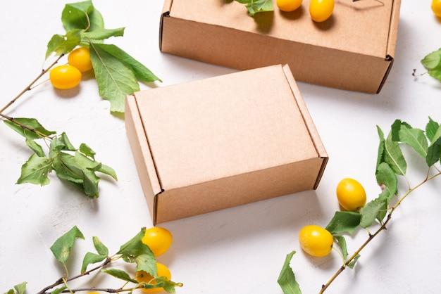 Caixa de papelão marrom com folhas verdes frescas
