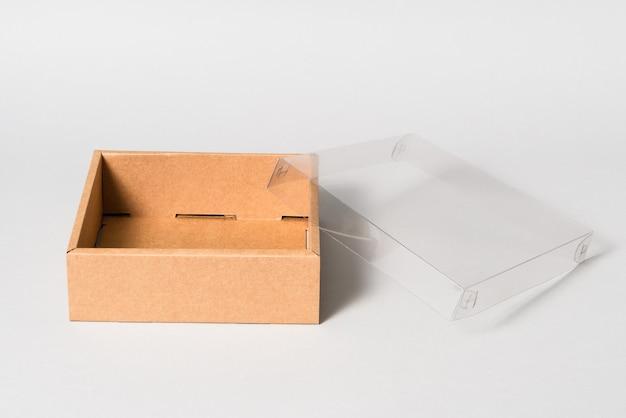 Caixa de papelão marrom com tampa transparente, isolada