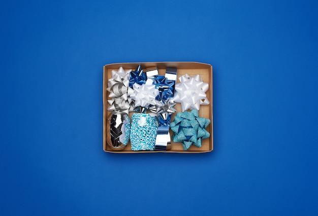 Caixa de papelão marrom com um conjunto de fitas de decoração e arcos para embrulhar presentes