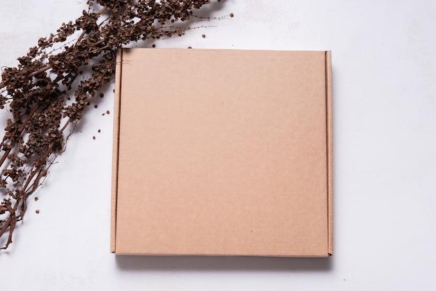 Caixa de papelão marrom decorada com simulação de galhos secos