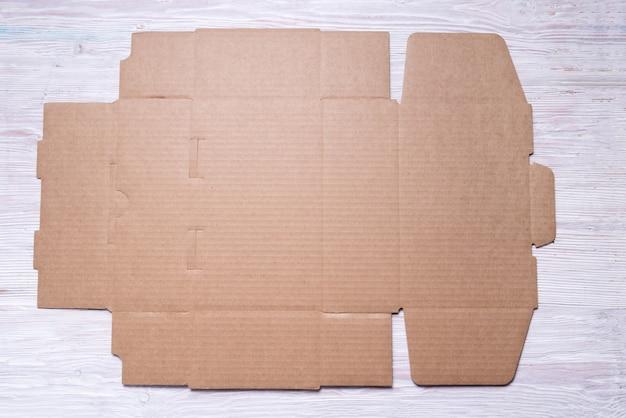 Caixa de papelão marrom desdobrada plana sobre fundo de madeira