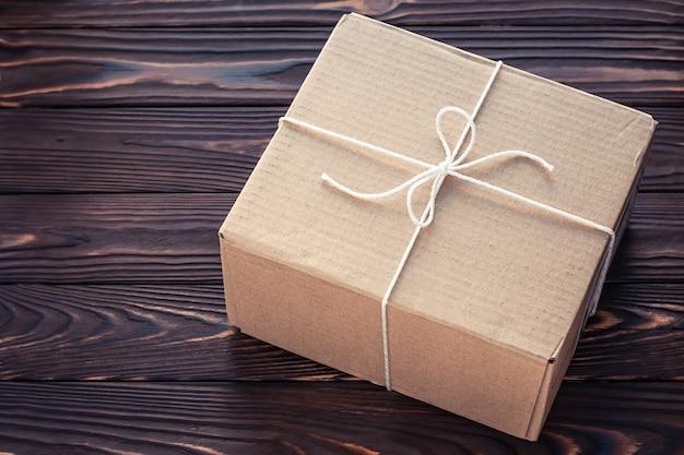 Caixa de papelão marrom em placas de madeira escuras. conceito de serviço de entrega de encomendas.