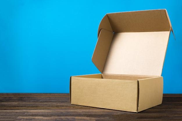 Caixa de papelão marrom fechada vazia para simulação em madeira escura