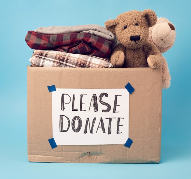 Caixa de papelão marrom grande com a inscrição, por favor doe, a caixa está cheia de várias roupas, brinquedos