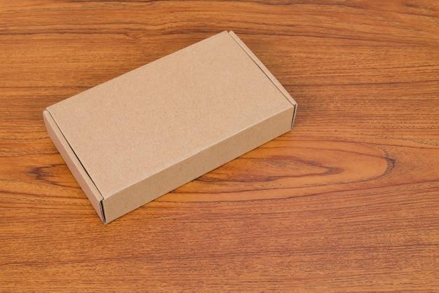 Caixa de papelão marrom vazia ou bandeja para mock-se na madeira
