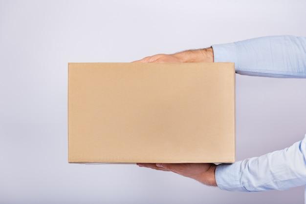 Caixa de papelão nas mãos masculinas. entrega de encomendas em casa. presente