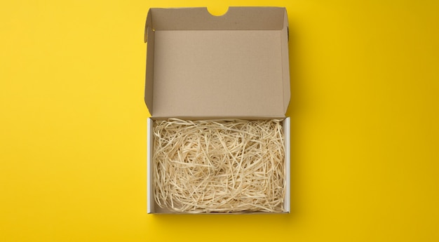 Caixa de papelão ondulado retangular aberta com serragem no interior. embalagem, contêineres para transporte em fundo amarelo